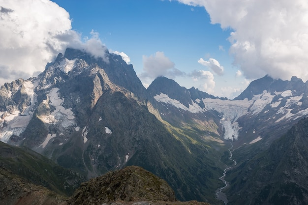 Panorama da cena de montanhas com céu azul dramático no parque nacional de dombay, cáucaso, na rússia. paisagem de verão e dia ensolarado