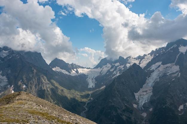 Panorama da cena de montanhas com dramático céu nublado no parque nacional de dombay, cáucaso, rússia. paisagem de verão e dia ensolarado