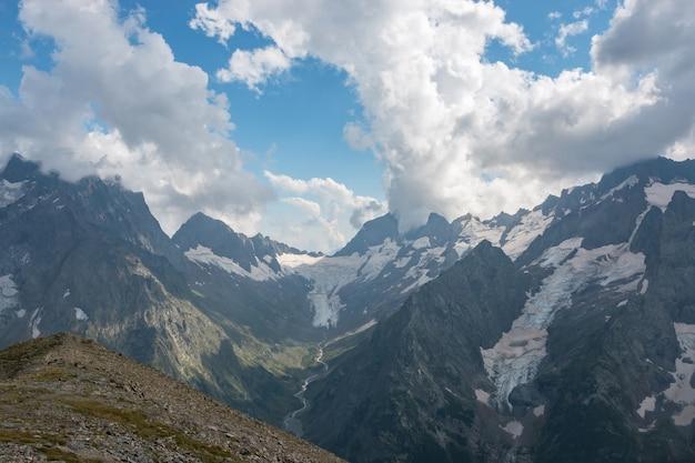 Panorama da cena de montanhas enevoadas com céu azul dramático no parque nacional de dombay, cáucaso, na rússia. paisagem de verão e dia ensolarado