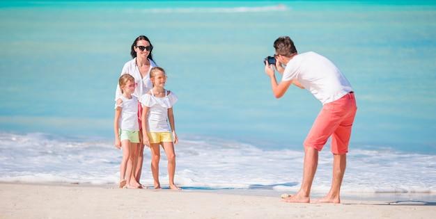 Panorama da família de quatro pessoas que toma uma foto do selfie em seus feriados da praia. férias de praia da família
