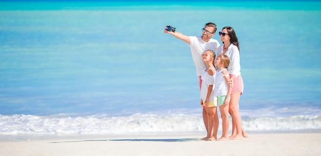 Panorama da família linda feliz na praia