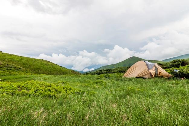Panorama da manhã fria de verão nevoento e tenda de caminhantes turísticos nas montanhas dos cárpatos