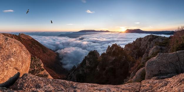 Panorama da montanha com nuvens no vale e pássaros voando alto no céu