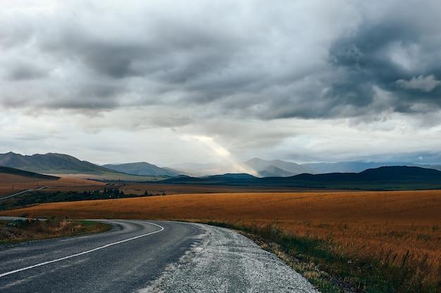 Panorama da montanha com um campo e céu nublado com a luz do sol