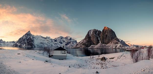 Panorama da montanha de neve com vila de pescadores ao pôr do sol