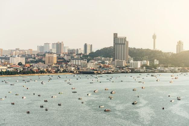 Panorama da paisagem urbana com edifícios de construção e vista do mar com barcos, céu brilhante e nuvens da praia de pattaya, tailândia