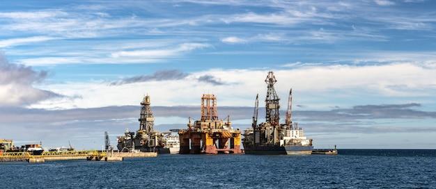Panorama da plataforma da perfuração para a exploração do petróleo no oceano com navios do transporte e o céu bonito.