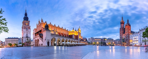 Panorama da praça do mercado medieval principal com a basílica de santa maria, o cloth hall e a torre da câmara municipal na cidade velha de cracóvia pela manhã Foto Premium