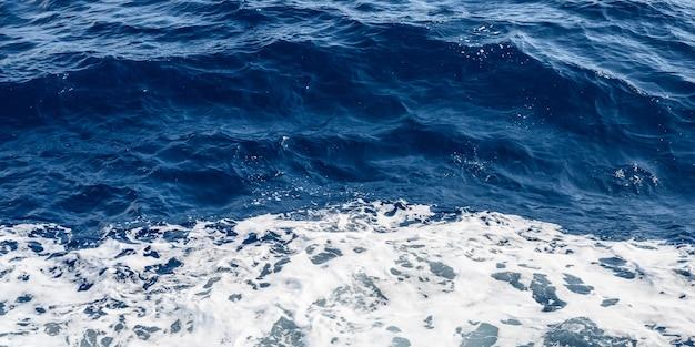 Panorama da superfície do mar azul com ondas pequenas e espaço de espuma branca para texto