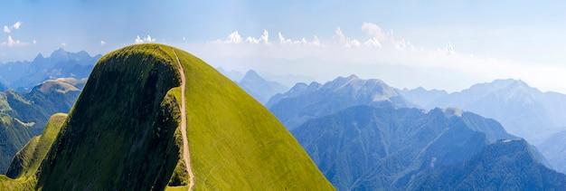 Panorama das colinas verdes nas montanhas de verão com estrada de cascalho para viajar de carro
