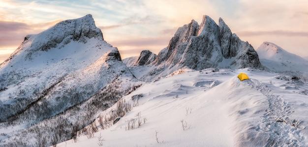 Panorama das montanhas de pico íngreme com neve coberta e tenda amarela
