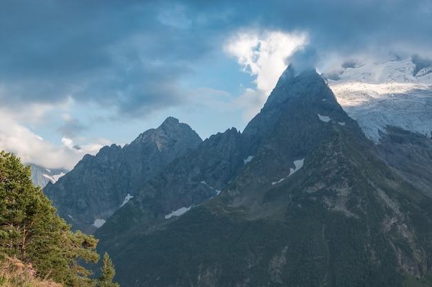 Panorama das montanhas e a cena da floresta no parque nacional de dombay, cáucaso, na rússia. paisagem de verão e dia ensolarado