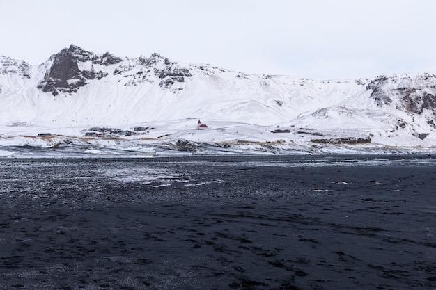 Panorama das montanhas islandesas perto da areia da praia de areia preta