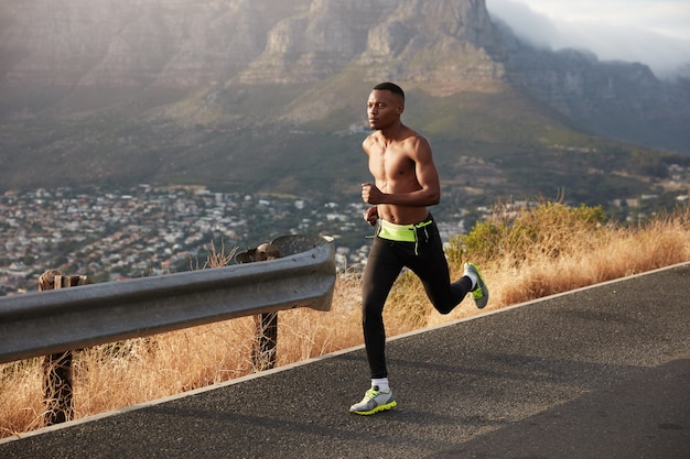 Panorama de banner de estilo de vida saudável. o homem afro-americano rápido faz exercícios aeróbicos, posa ao ar livre, usa legging e tênis, gosta de velocidade e ar puro em montanhas rochosas. exercício ao ar livre.