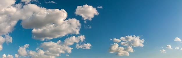 Panorama de céu azul profundo com nuvens raras iluminadas pela luz do sol