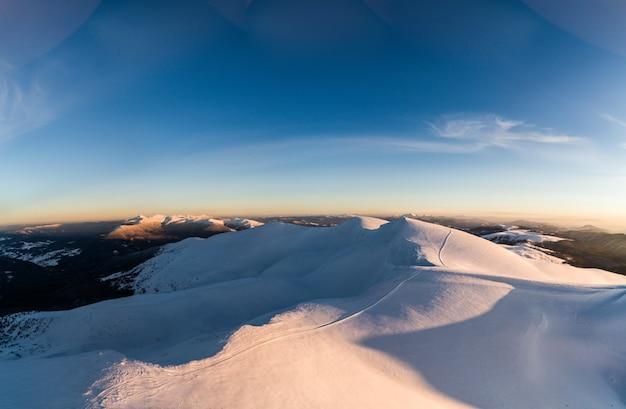 Panorama de dia maravilhoso com montes de neve nas montanhas entre as florestas em um dia ensolarado e nevoento