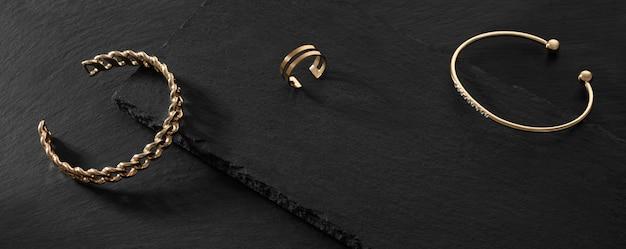 Panorama de duas pulseiras modernas e anel de ouro sobre fundo de pedra