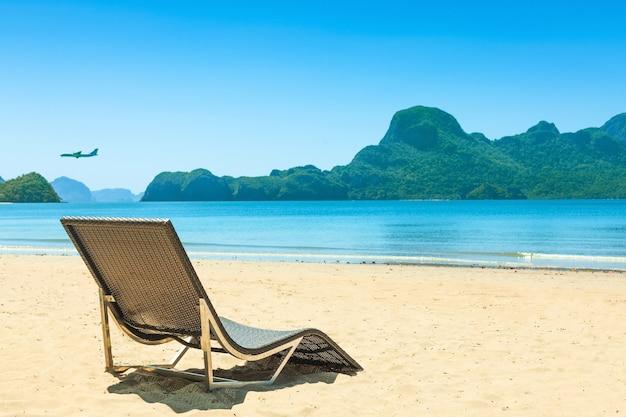 Panorama de espreguiçadeiras em uma bela praia tropical com pedras