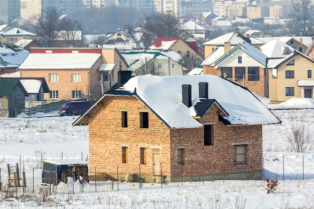 Panorama de inverno amplo de terreno rural para desenvolvimento em tranquila área suburbana residencial. casa de tijolo nova não terminada da vila distante e edifícios da cidade alta sob o céu azul.