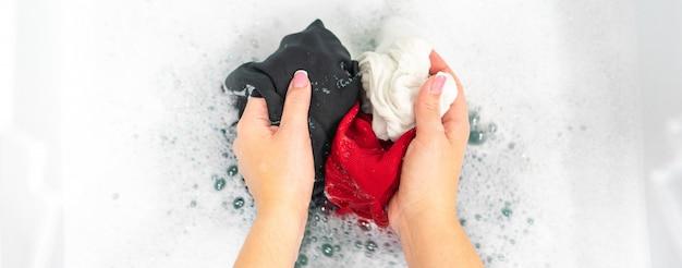 Panorama de mãos femininas lavando roupas pretas, vermelhas e brancas em espuma branca