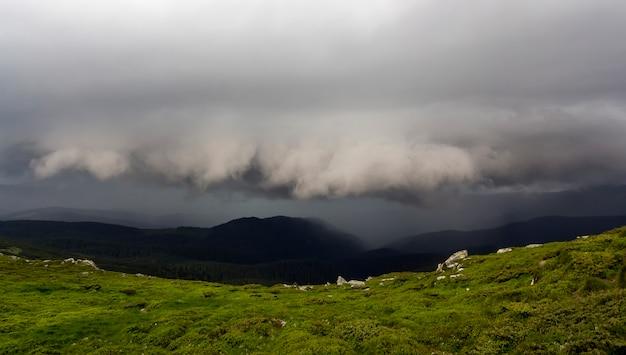 Panorama de montanha amplo verão antes da tempestade. nuvens escuras de chuva baixas sobre o vale verdejante e rochoso e a cordilheira distante, coberta por uma densa floresta sempre verde. beleza do conceito de natureza.