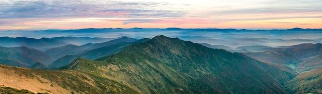 Panorama de montanhas verdes e colinas sobre o dramático céu ao pôr do sol