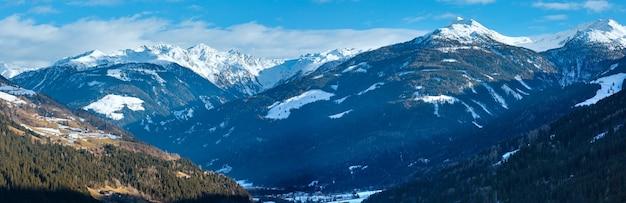 Panorama de país de montanha de inverno com aldeia na encosta (áustria).