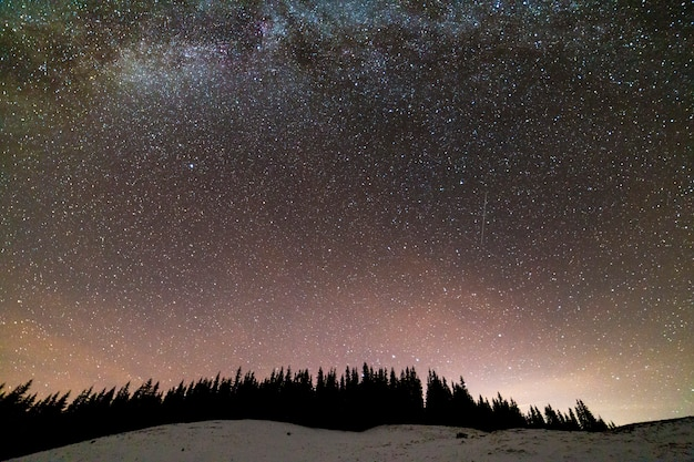 Panorama de paisagem de noite de montanhas de inverno. constelação brilhante da via láctea no céu estrelado azul escuro sobre a floresta de pinheiros de abeto vermelho escuro, brilho suave no horizonte após o pôr do sol.