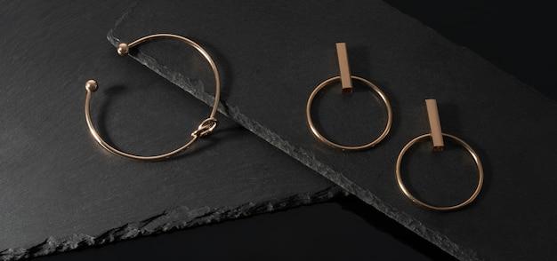 Panorama de par de pulseira e brincos em forma de nó na superfície de pedra preta