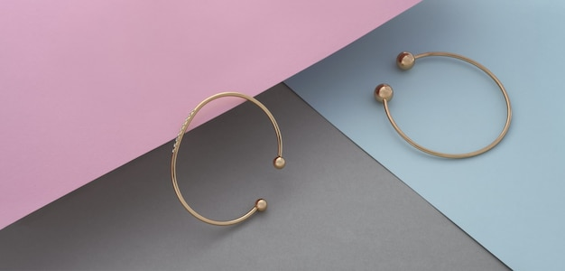 Panorama de two moderno dourado com pulseiras de diamantes em fundo de cor pastel com espaço de cópia