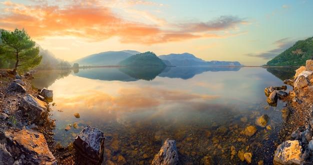 Panorama de um lago de montanha com uma costa rochosa ao pôr do sol