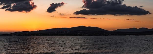 Panorama de um pôr do sol colorido do mar, que se passa sem problemas atrás das montanhas. paisagem nublada e escura