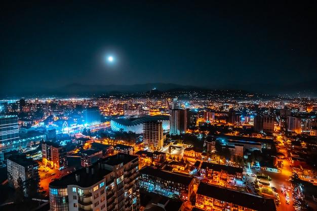 Panorama de uma cidade de noite luminosa iluminada por uma lua brilhante