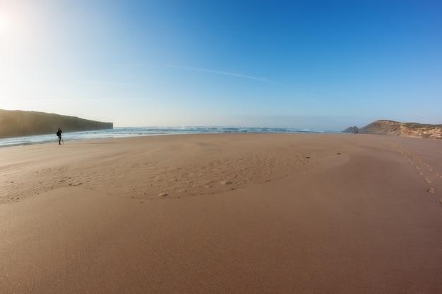 Panorama de uma praia arenosa e um fotógrafo trabalhando em frente ao mar.