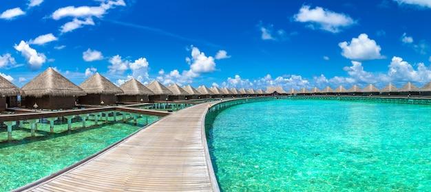 Panorama de water villas e ponte de madeira em uma praia tropical