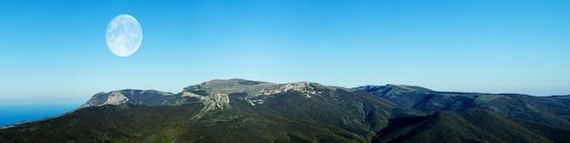 Panorama deslumbrante da paisagem da montanha contra o céu azul e lua cheia ao anoitecer