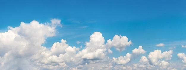 Panorama do céu azul com nuvens brancas encaracoladas alinhadas em uma fileira