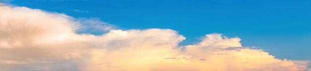 Panorama do céu azul com nuvens leves e fofas ao pôr do sol