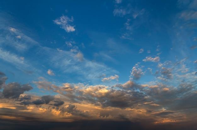 Panorama do céu no nascer ou pôr do sol. a vista bonita das nuvens azuis escuras iluminou-se pelo sol brilhante do amarelo alaranjado no céu claro. beleza e poder da natureza, meteorologia e conceito de mudança climática.