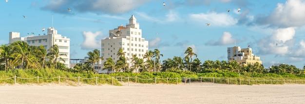 Panorama do distrito art deco de south beach miami. os edifícios são cercados por palmeiras tropicais.
