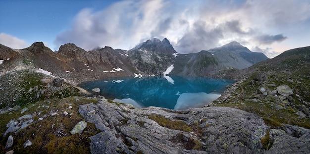 Panorama do lago de montanha azul alto nas montanhas