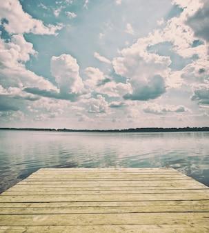 Panorama do lago e cais de madeira na costa