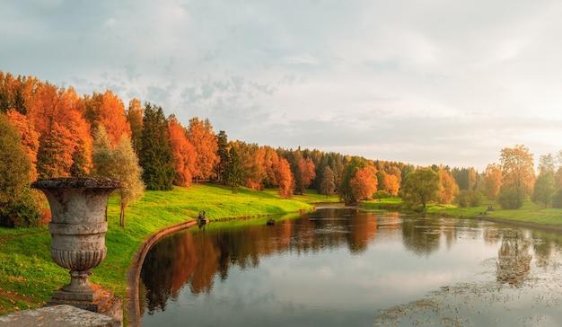 Panorama do parque de outono com vaso de pedra vintage e árvores vermelhas à beira do lago