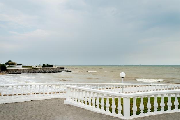 Panorama do passeio com um parapeito em um dia ensolarado à beira-mar.