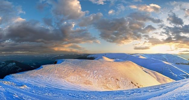 Panorama do por do sol do cume da montanha em cores douradas vista dos raios de sol da noite passada (ucrânia, montanhas dos cárpatos, estação de esqui de drahobrat). imagem de ponto de vários tiros.