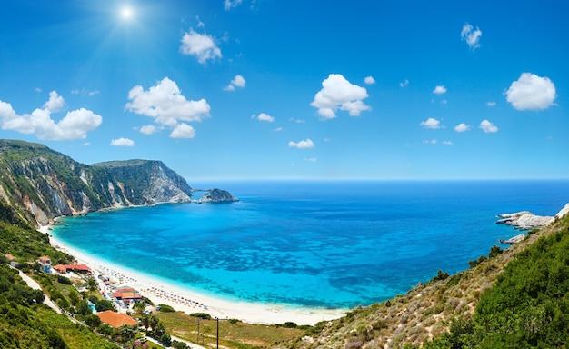Panorama do verão da praia de petani kefalonia, grécia. céu azul profundo com algumas nuvens cúmulos e luz do sol