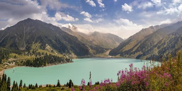 Panorama incrível do lago grande almaty num dia ensolarado de verão com céu nublado, natureza do cazaquistão.