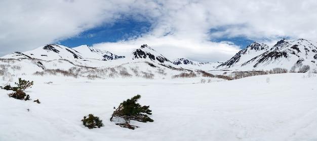 Panorama inverno montanha rochosa paisagem vista da cordilheira nevada e nuvens brancas no céu azul