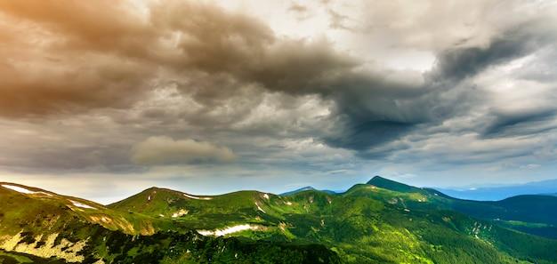 Panorama largo do iluminado pelo vale verde do sol da manhã, colinas cobertas com floresta e montanhas enevoadas distantes com manchas de neve sob o céu nublado e ventoso. beleza da natureza, turismo e conceito de viagem.