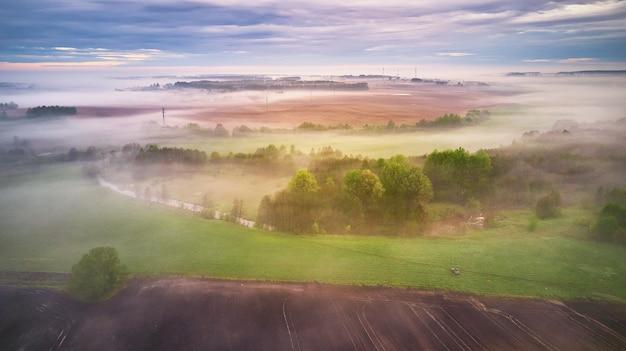 Panorama nublado de manhã chuvosa nublado de verão. rio enevoado rural, campos, prados, aldeia. tempo nublado de primavera. árvores e arbustos florescendo. bielo-rússia, região de minsk